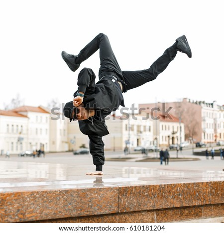 34050e0357dd Handsome man in sunglasses and black modern clothes is dancing in the city.