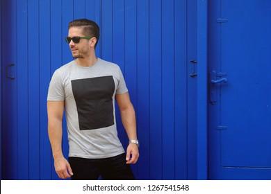 Hombre guapo con gafas de sol delante de una pared de madera de fondo azul. Lleva pantalones de verano con un cuadrado negro en el pecho y un reloj metálico de plata.