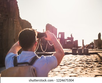 Handsome man in sunglasses holding a smartphone in his hands against the backdrop of historic ruins, blue sky and the rays of the setting sun. Italy, Pompeii. Travel, leisure and technology concept