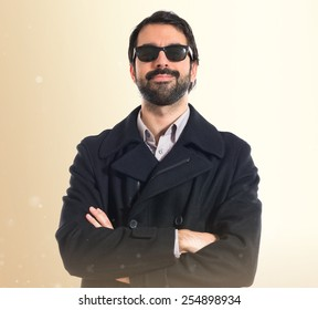 Handsome man with sunglasses over ocher background