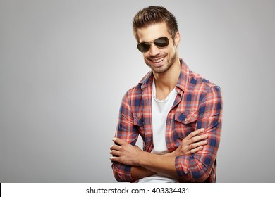 Handsome man with sunglasses posing in the studio on a light gray background