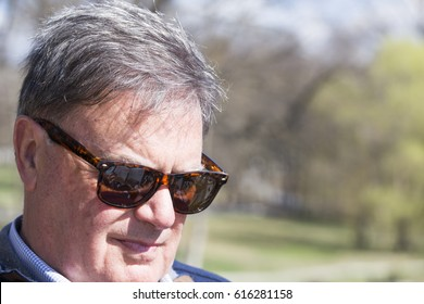 Handsome man in sunglasses sitting in park reading a book