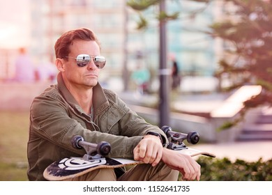 Handsome man with sunglasses sitting with skateboard looking cool