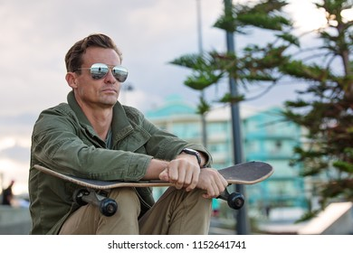 Handsome man with sunglasses sitting with skateboard on knees looking cool