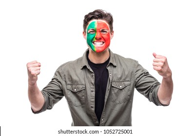 Handsome man supporter fan of Portugal national team painted flag face get happy victory screaming into a camera.