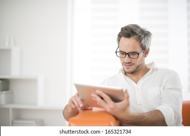 handsome man surfing on tablet on a couch