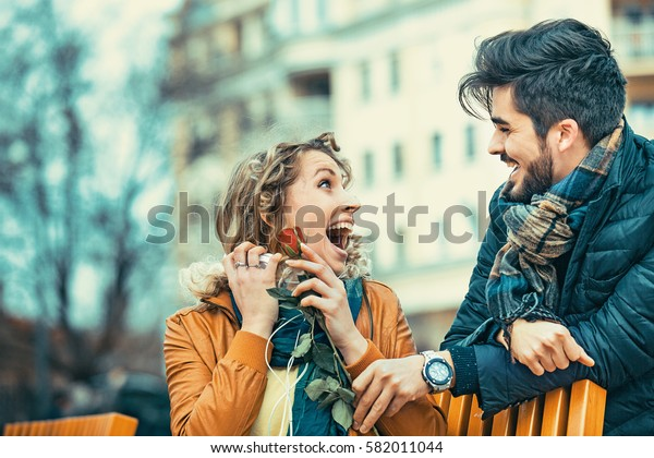 Handsome man surprising his girlfirend with rose.