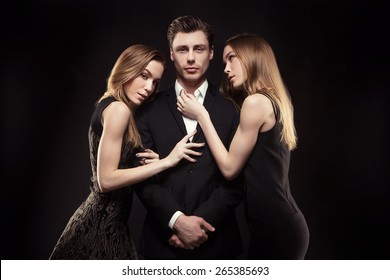 handsome man surrounded by beautiful girls in the studio. concept of success, 2 girls, twins