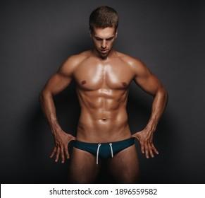 Handsome man in swimsuit. Male model in studio. Sexy guy in briefs.