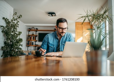 Handsome man taking notes and looking at laptop, at home office, portrait.