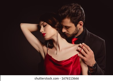 Handsome man taking off dress from elegant girlfriend isolated on black