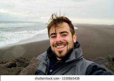 Handsome man taking selfie at black sand beach in Iceland