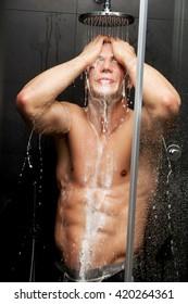 Handsome man taking the shower.
