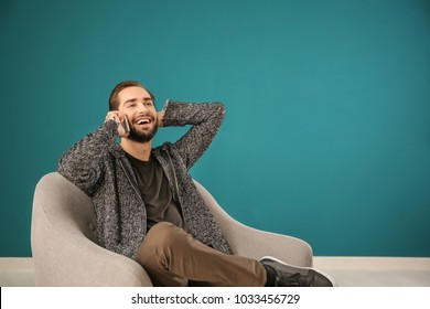 Handsome man talking on mobile phone while sitting in comfortable armchair against color wall