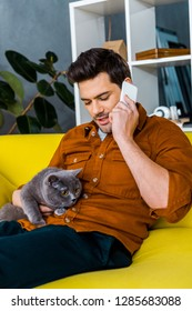 handsome man talking on smartphone while sitting on sofa and looking at cat