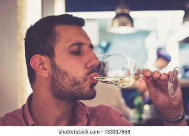 Handsome man tasting a glass of white wine in a fish restaurant