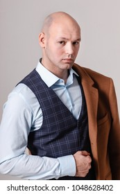 Handsome man in a three piece suit with a shoulder-clad coat posing on a cyclorama