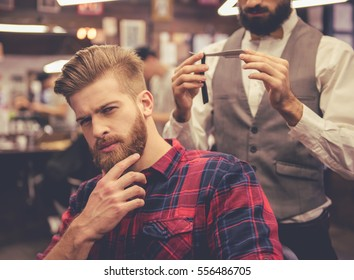 Handsome man is touching his beard while sitting in chair at the barbershop, in the background barber is holding a straight razor