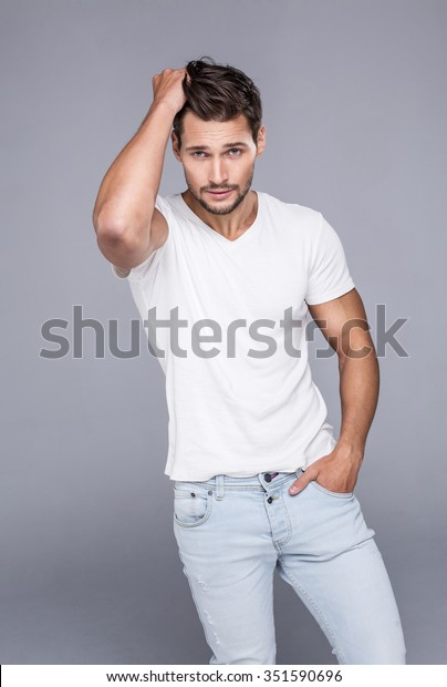 Handsome man touching his hair. Fashion model posing in white t-shirt looking at camera and touching his hair