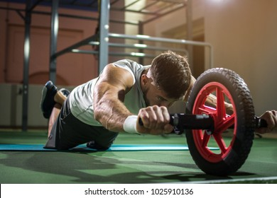 Handsome man training with wheel to strengthen his abdominal muscle.