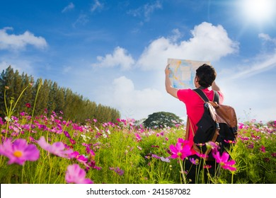 Handsome man Traveling to Tote Bag Viewing Map for a field trip on flower Cosmos