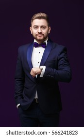 Handsome man in tuxedo and bow tie looks at watch. Fashionable, festive clothing. emcee on dark background