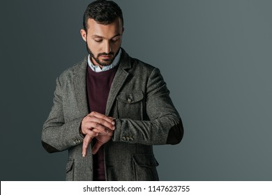 handsome man in tweed jacket looking at wristwatch, isolated on grey