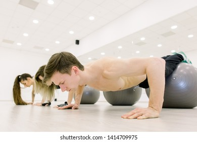 Handsome man and two girls in sportswear perform pushups on gray fitballs at the gym.