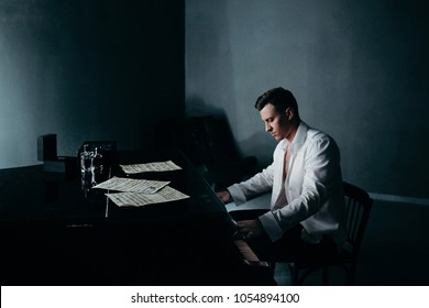 A handsome man in an unbuttoned white shirt is playing on a black piano in a gray dark room