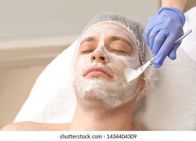 Handsome man undergoing treatment with facial mask in beauty salon