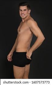 Handsome man in underwear on black background