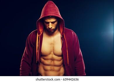 Handsome man in an unzipped red hoodie in studio on dark background