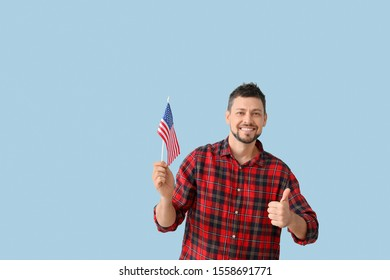 Handsome man with USA flag showing thumb-up on color background. Memorial Day celebration