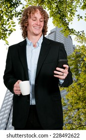 Handsome man using a cell phone for texting while drinking coffee
