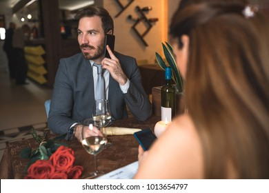 Handsome man using cellphone while sitting with his girlfriend in restaurant