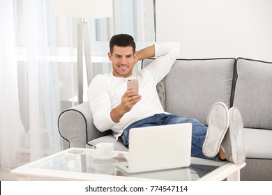 Handsome man using cellphone while resting on sofa at home