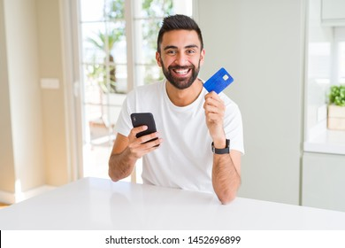 Handsome man using credit card to pay online with smartphone