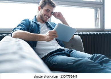 Handsome man is using a digital tablet and smiling while resting on couch at home.
