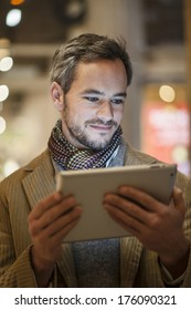 handsome man using a digital tablet outside with city lights at the background