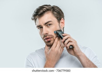 handsome man using electric razor, isolated on grey
