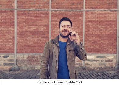 handsome man is using his smartphone device talking in front of a brick wall