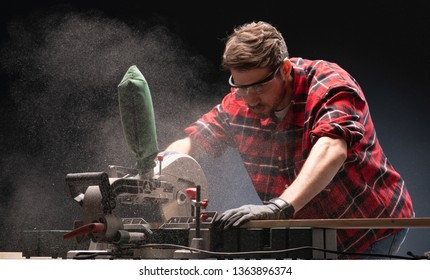 Handsome man using modern electric circular saw for ctting wood  in the workshop