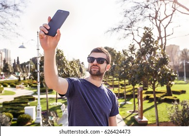 Handsome man using phone.Man in sunglasses,Bearded Man Takes Selfie,casual wear,blue shirt,pretty face,hipster,attractive,man at the park,Outdoor portrait of man,stylish outfit,Guy with smartphone