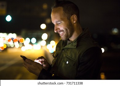A Handsome man using smart phone mobile in the city at night