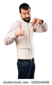 Handsome man with vest making good-bad sign on isolated white background