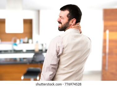 Handsome man with vest with neck pain inside house