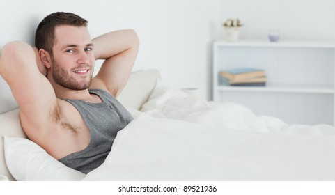 Handsome man waking up in his bedroom