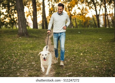 Handsome man walking his dog in the park.
