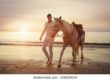 Handsome man walking on the beach with a horse