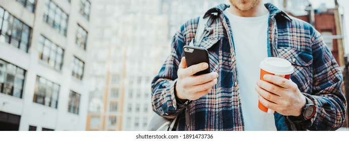 Handsome man walking on the urban street sidewalk with cup of hot coffee and texting on mobile phone. Close-up. Wide screen, panoramic